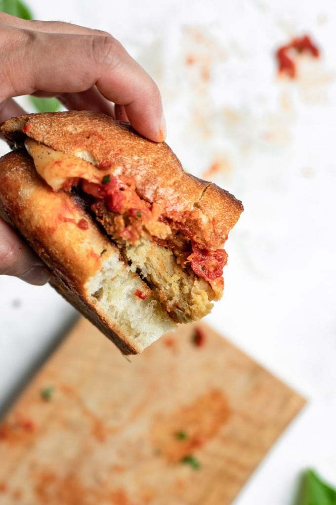 vegan chicken parmesan sandwich with a bite taken out of it