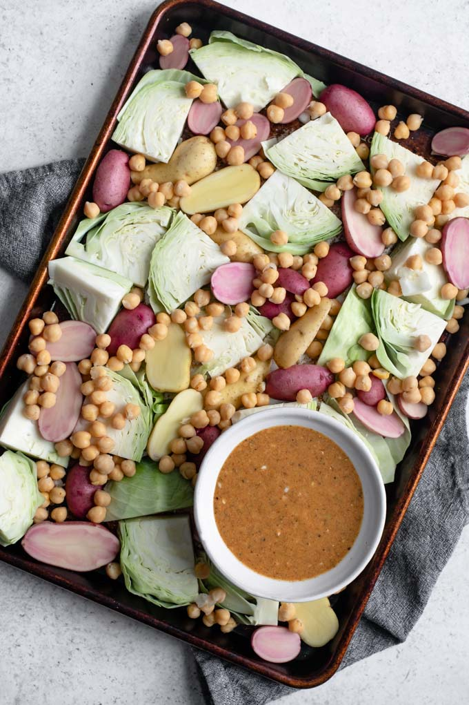cabbage, potatoes, and chickpeas on a sheet pan with a bowl of mustard vinaigrette on the side