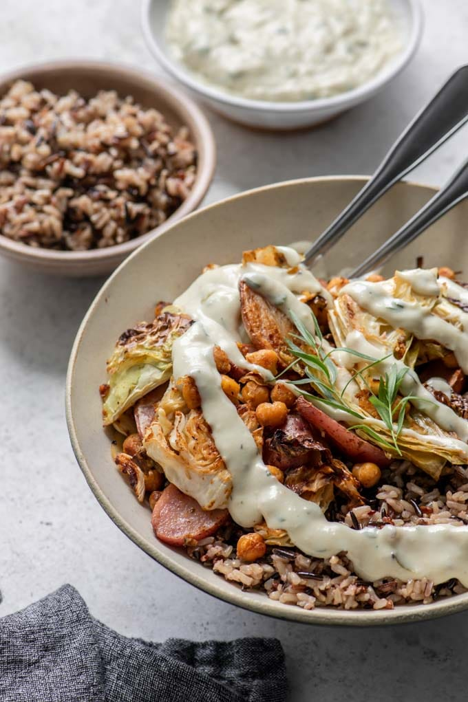 vegan cabbage sheet pan dinner with tarragon cream gravy drizzled overtop