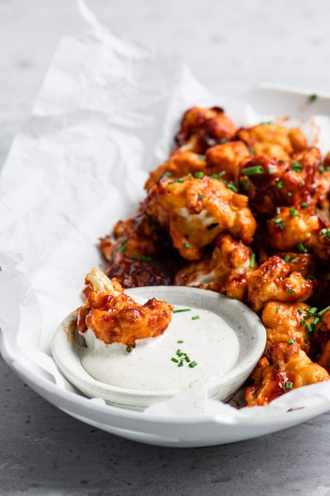 a cauliflower wing dipped into vegan ranch dressing