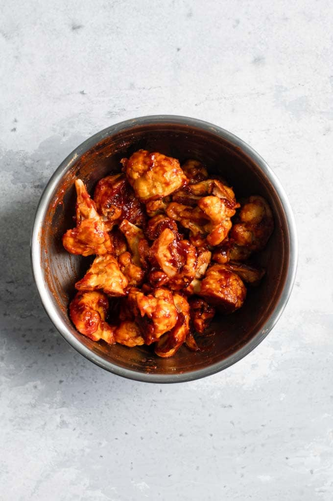 cauliflower wings tossed in cranberry barbecue sauce in a mixing bowl