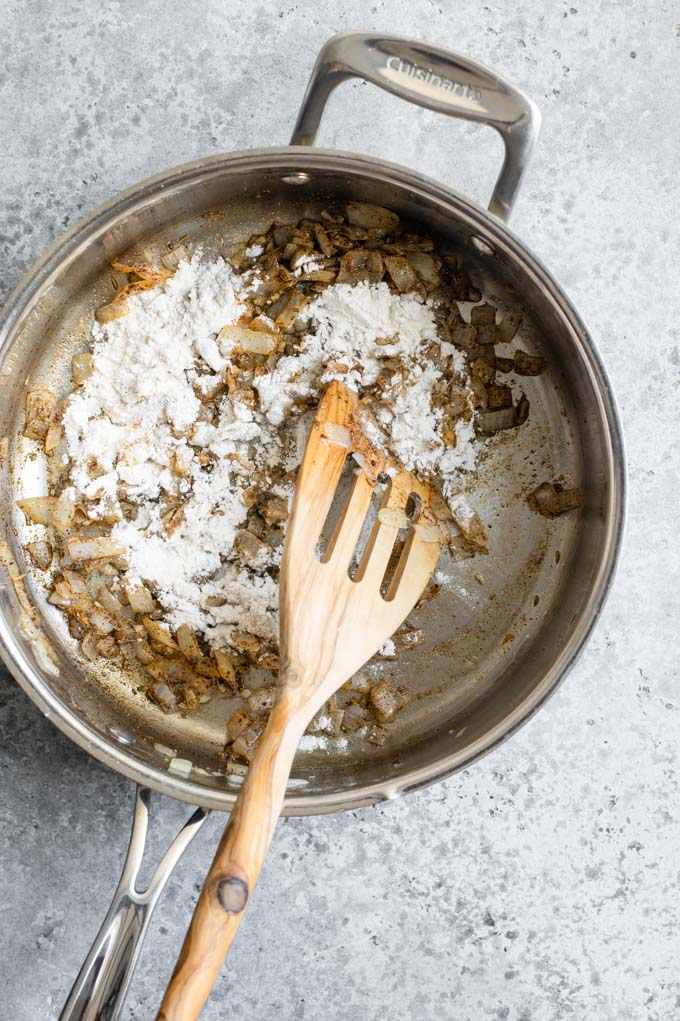 add flour to onion, garlic, and spices in pan