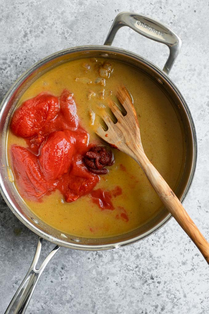 adding tomatoes and tomato paste to sauce