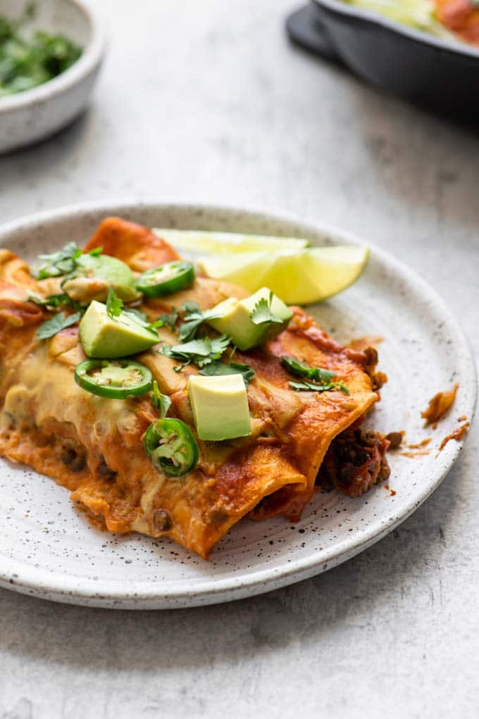 enchiladas on a plate served with lime
