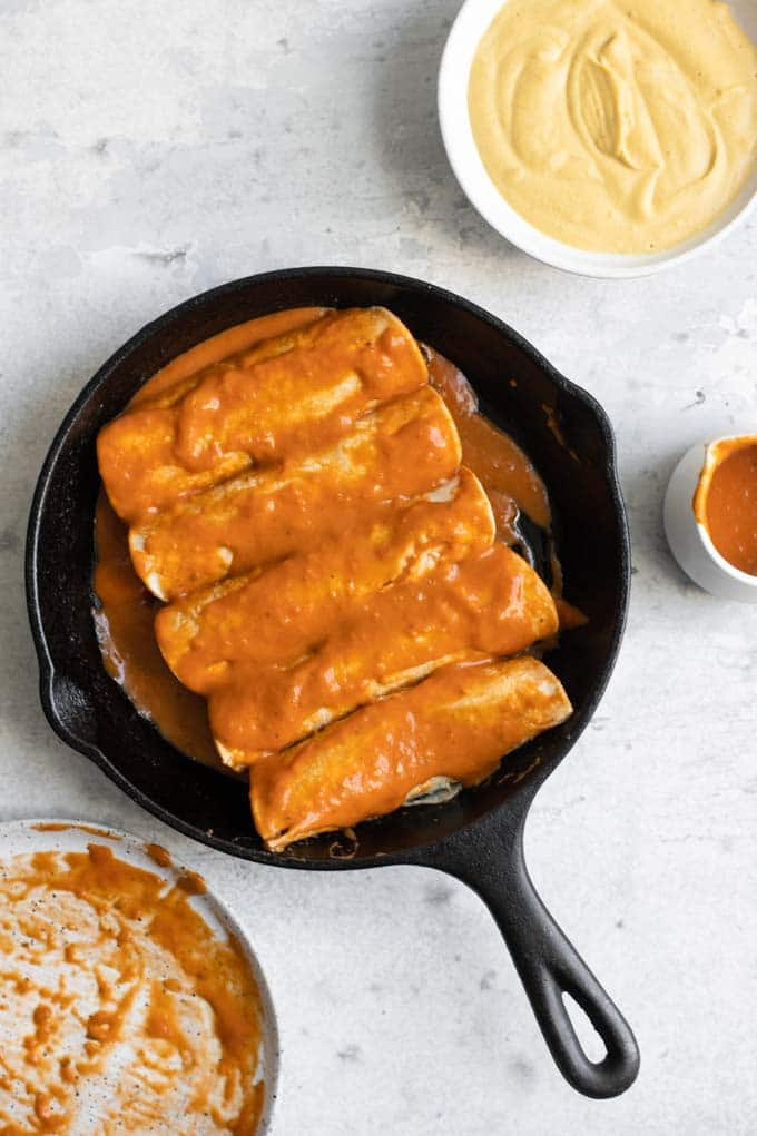 tortillas stuffed with lentil filling and smothered in enchilada sauce in a skillet