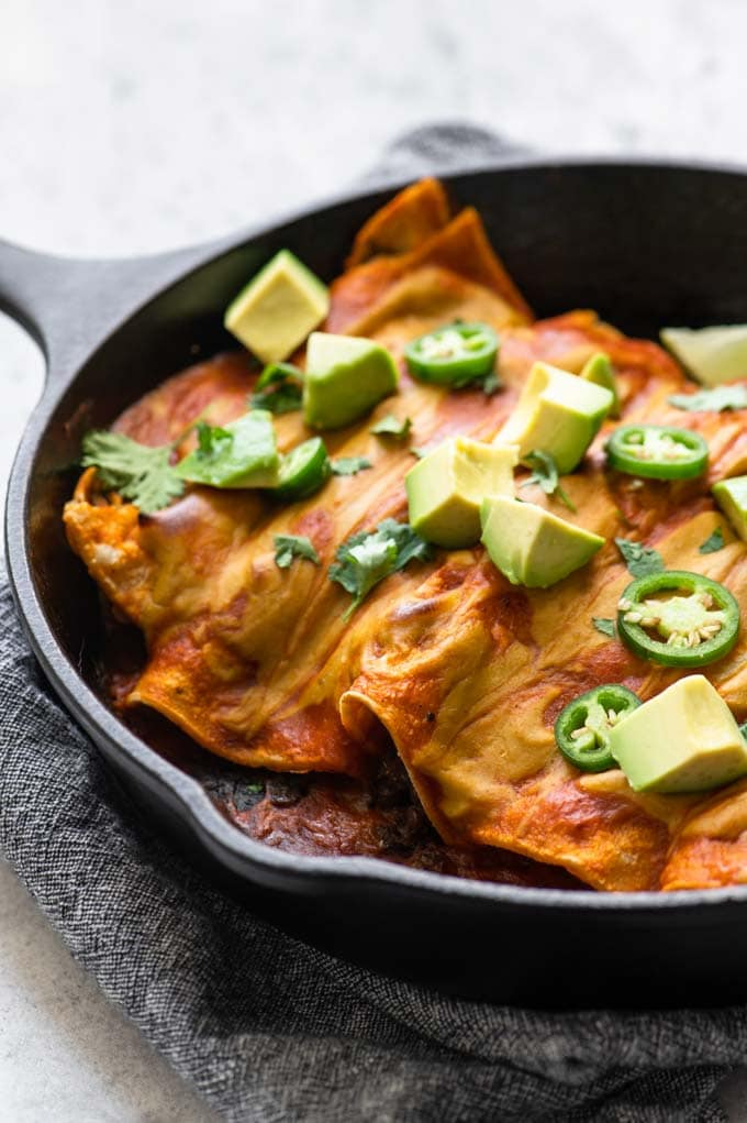 enchiladas baked in a skillet and topped with avocado and jalapeño