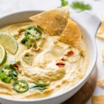 chips dipped into butternut queso