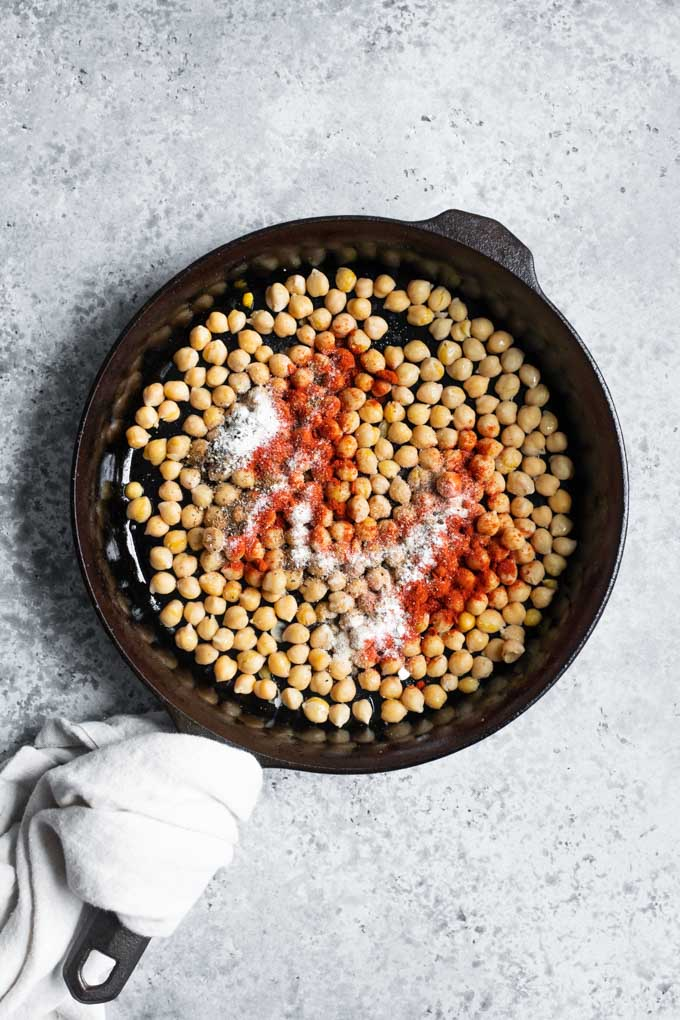 chickpeas in a skillet with chorizo spices sprinkled on top