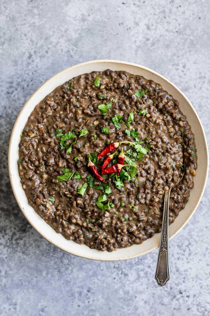 garlic urad dal fry in a serving bowl garnished with cilantro and dried red chiles