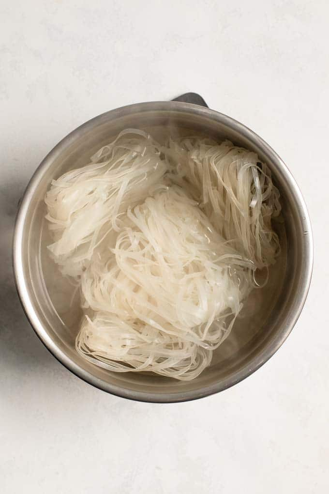 dry rice noodles submerged in boiling water