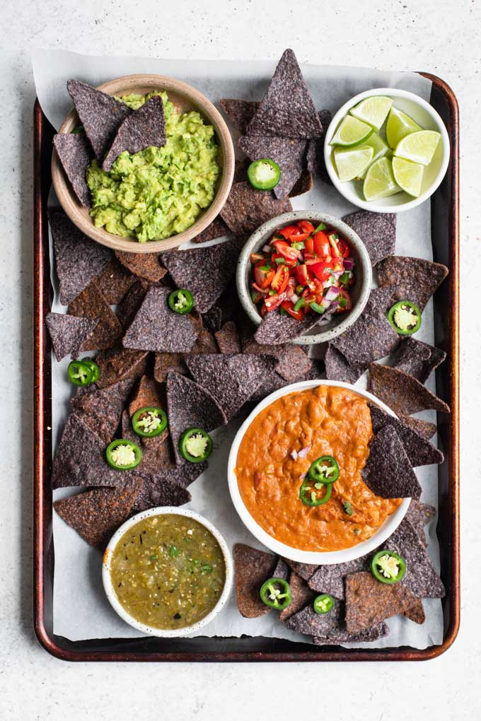 chip and dip spread with blue corn chips, bean dip, pico de gallo, salsa verde, and guacamole