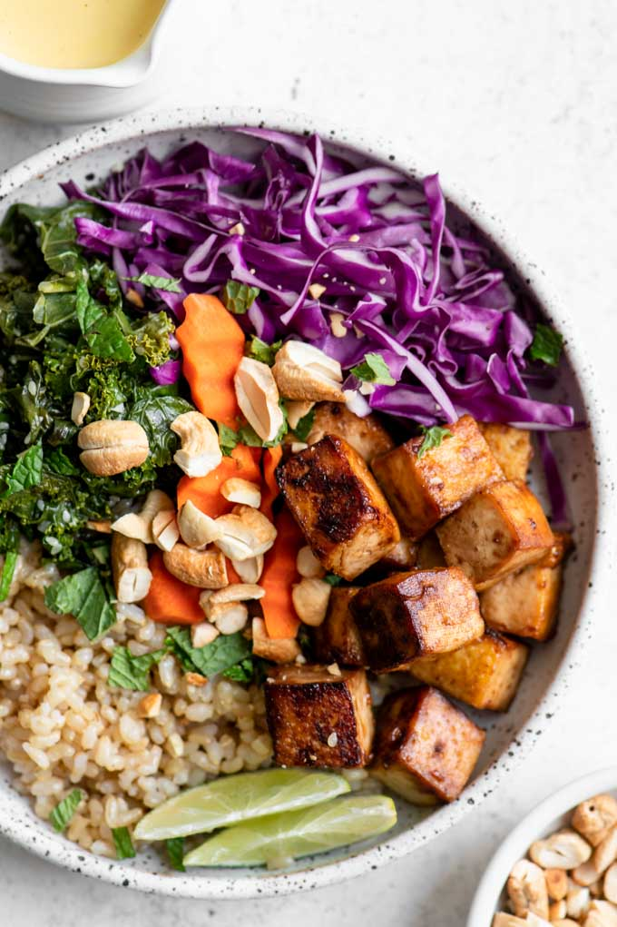 close up of the tofu buddha bowl with sesame kale, red cabbage, carrots, brown rice, toasted cashews and lime wedges