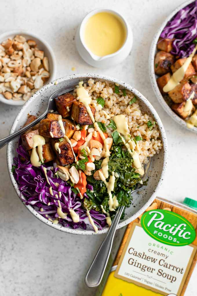 tofu buddha bowls drizzled with carrot ginger dressing and the box of Pacific Foods Cashew Carrot Ginger Soup used to make dressing