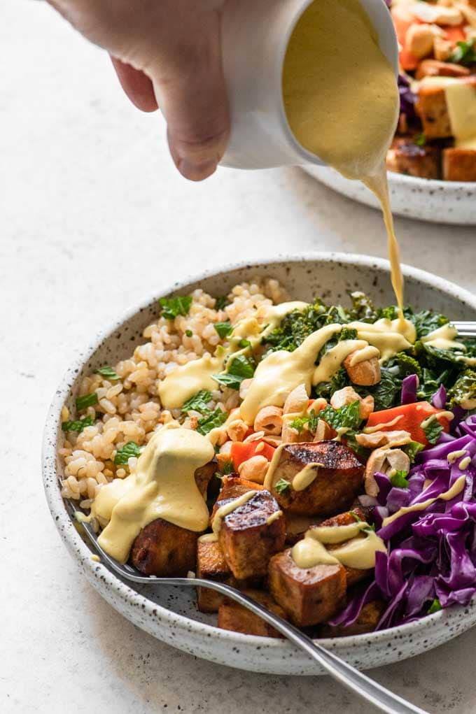 pouring dressing over tofu bowls