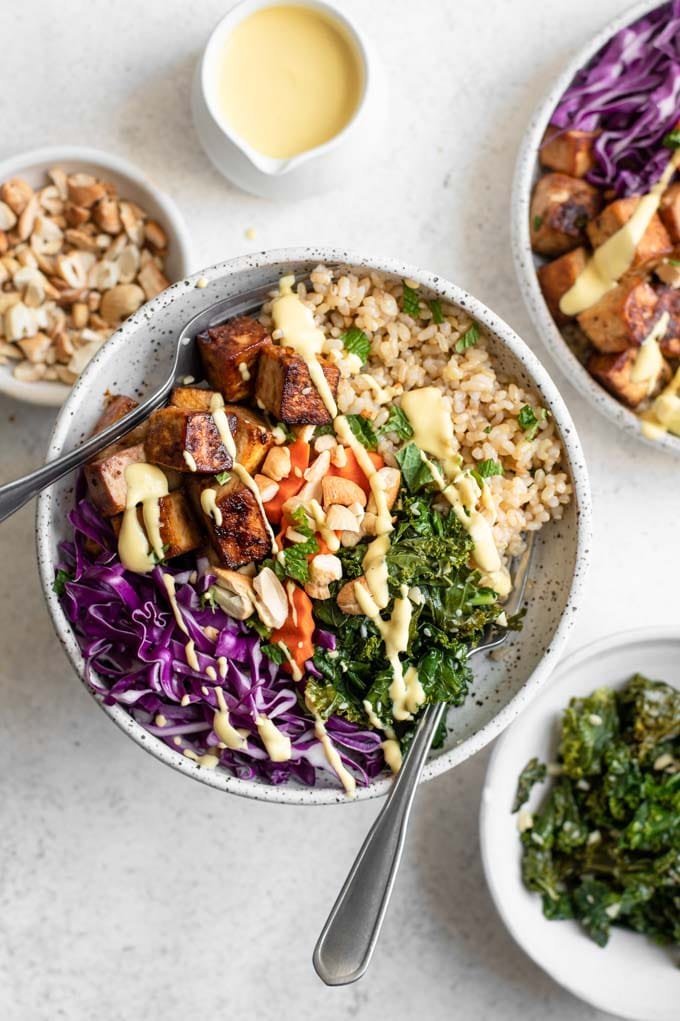 tofu buddha bowls with carrot ginger dressing and bowls of sesame kale and roasted cashews