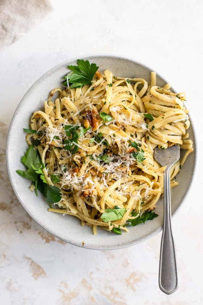walnut parsley linguine garnished with vegan parmesan and fresh parsley