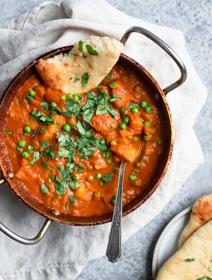 Indian spiced potatoes and peas curry served with garlic naan