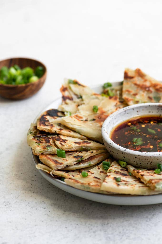 scallion pancakes on a plate with dipping sauce