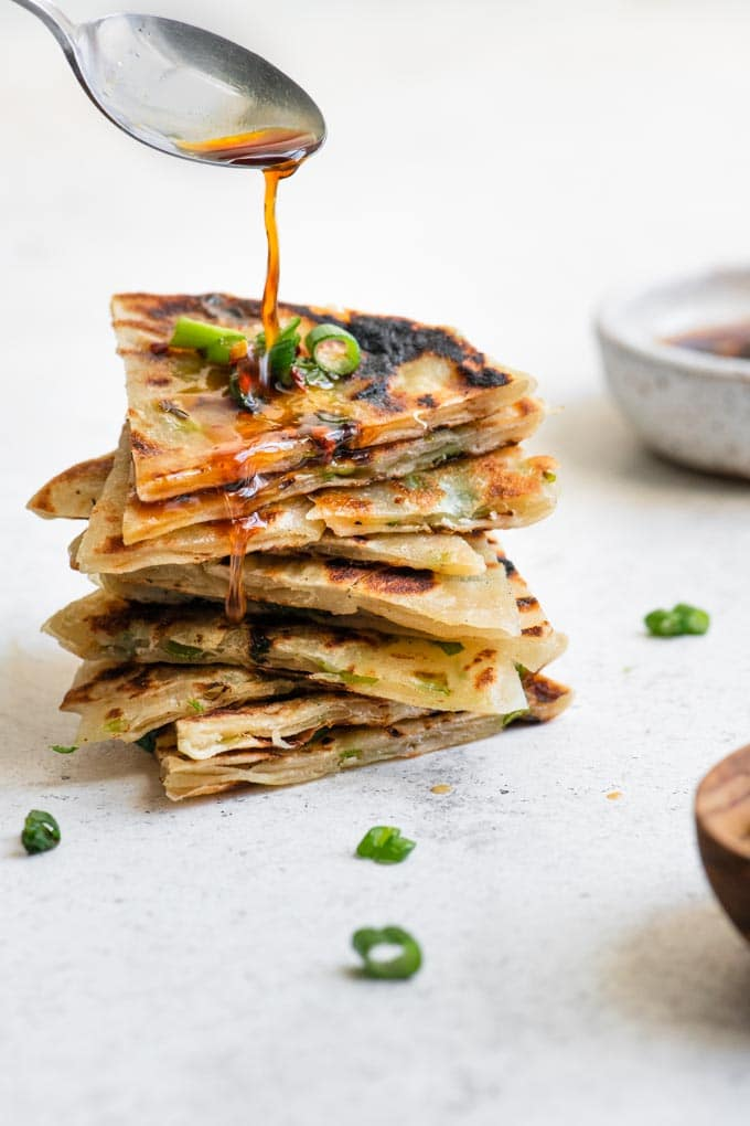 drizzling dipping sauce over a stack of scallion pancake wedges