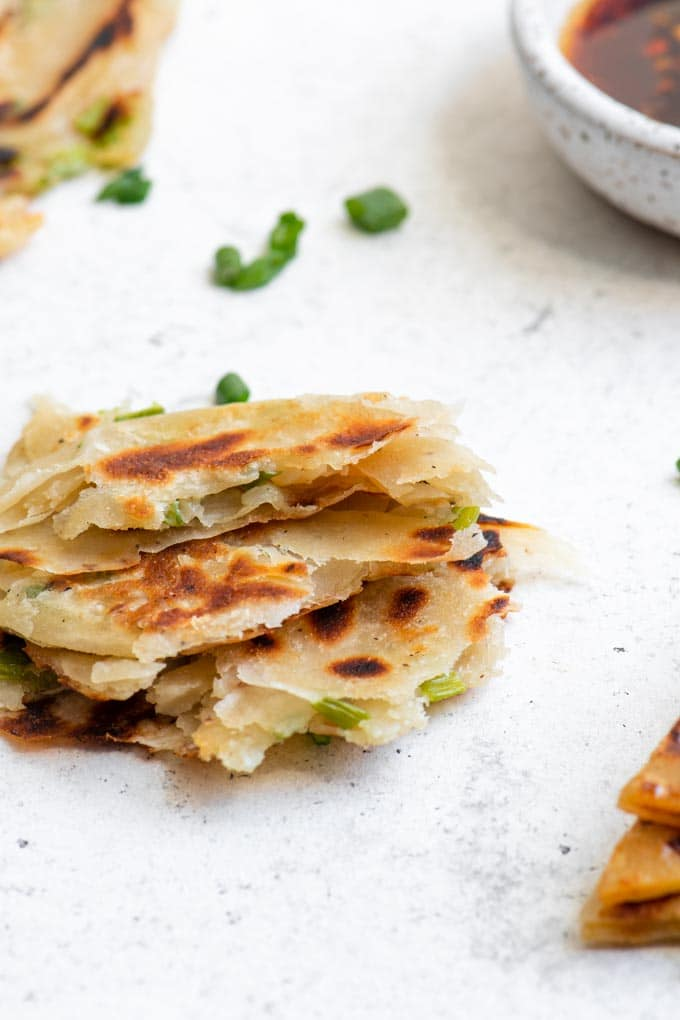 scallion pancake torn into pieces to show the flaky layers
