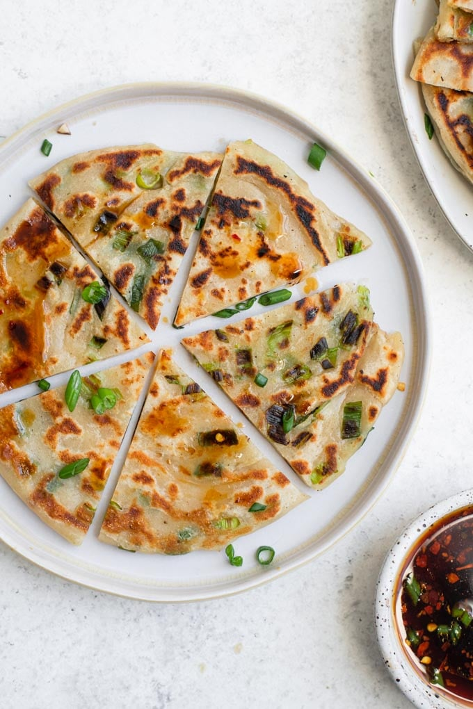 one scallion pancake cut into 6 wedges on a plate