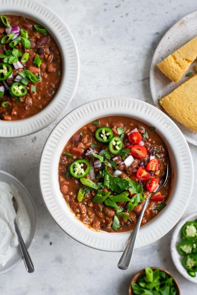 vegan chili with toppings and cornbread
