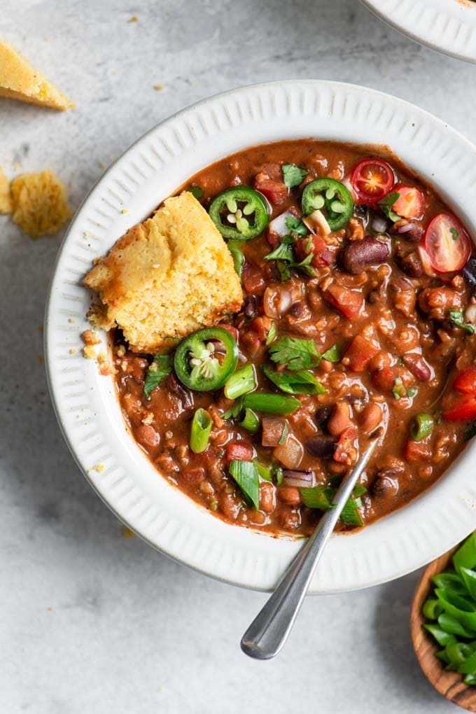 vegan chili with toppings mixed into the stew and a piece of cornbread tucked into the bowl