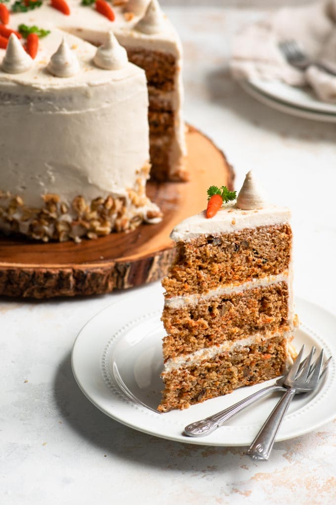 slice of carrot cake upright on a plate and full cake in the background