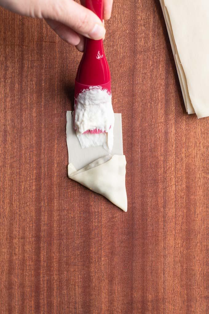 brushing samosa wrapper edge with flour water glue