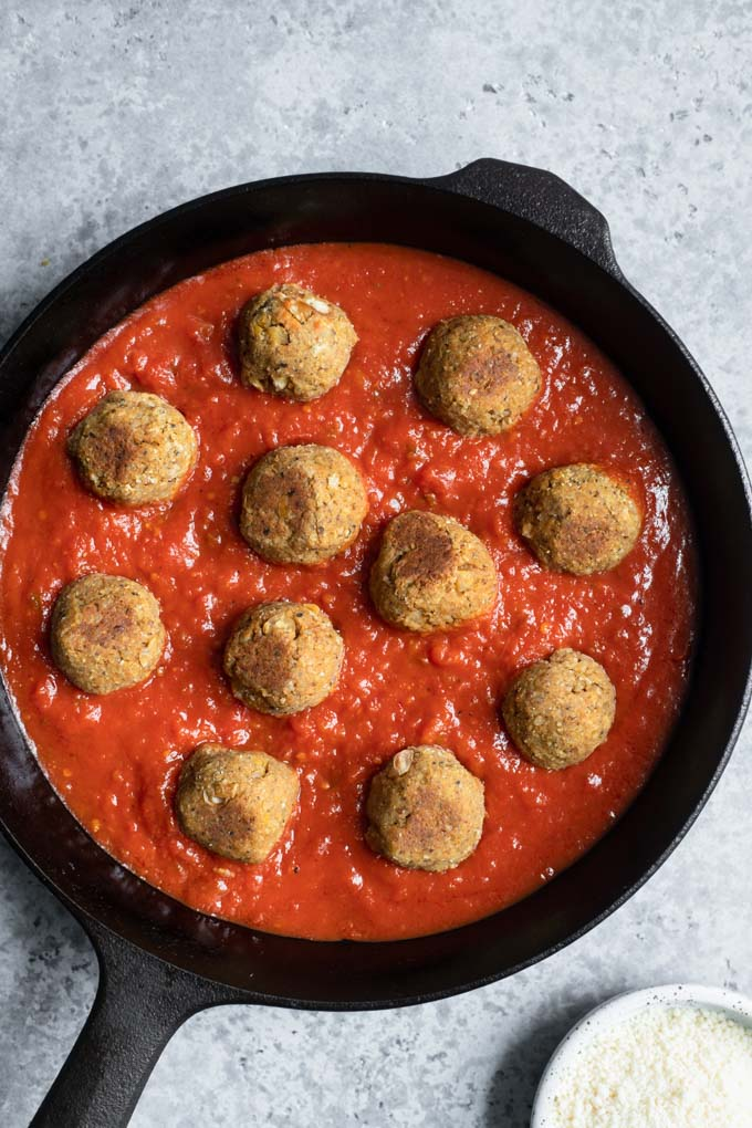 chickpea meatballs placed in pan with tomato sauce, before cooking
