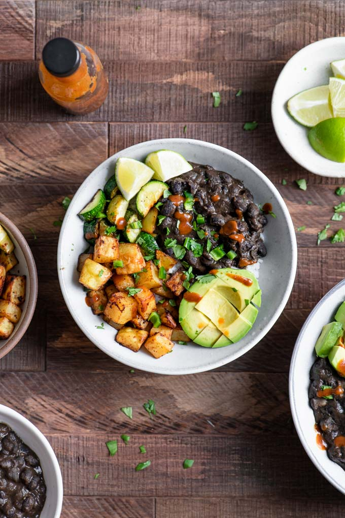 black bean burrito bowl with roasted potatoes, avocado, and zucchini