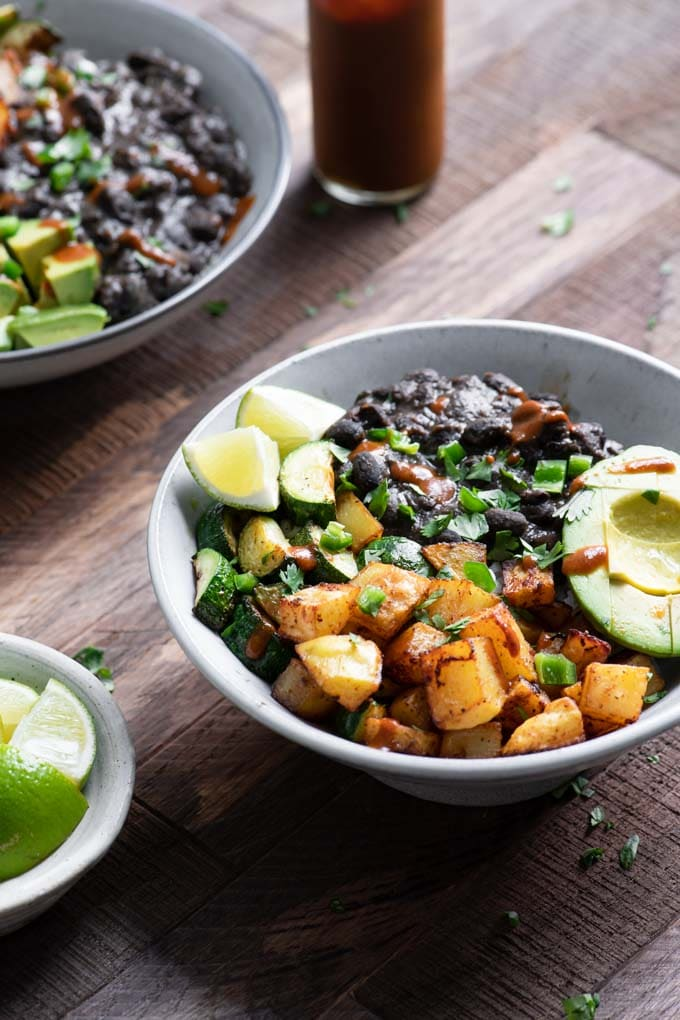 rice bowl with seasoned black beans, ancho roasted potatoes, zucchini, lime wedges, and rice
