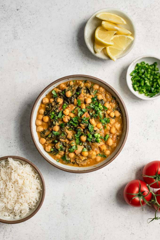 chickpea curry served with rice, lemon wedges, and minced pepper