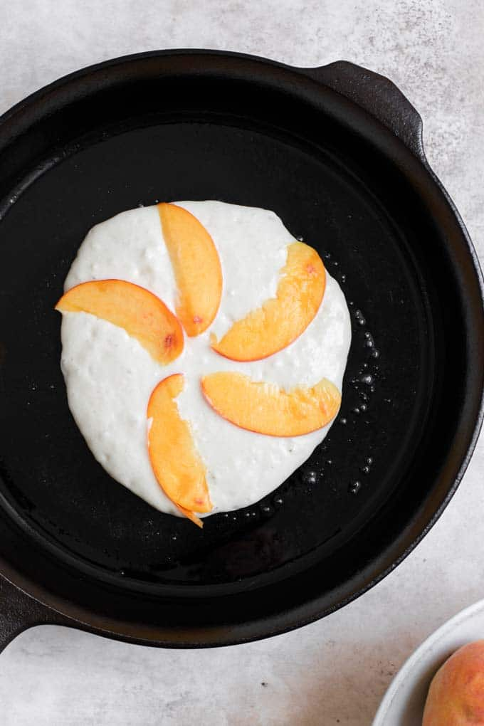pancake on skillet with 5 slices of peach arranged on top in a fan pattern
