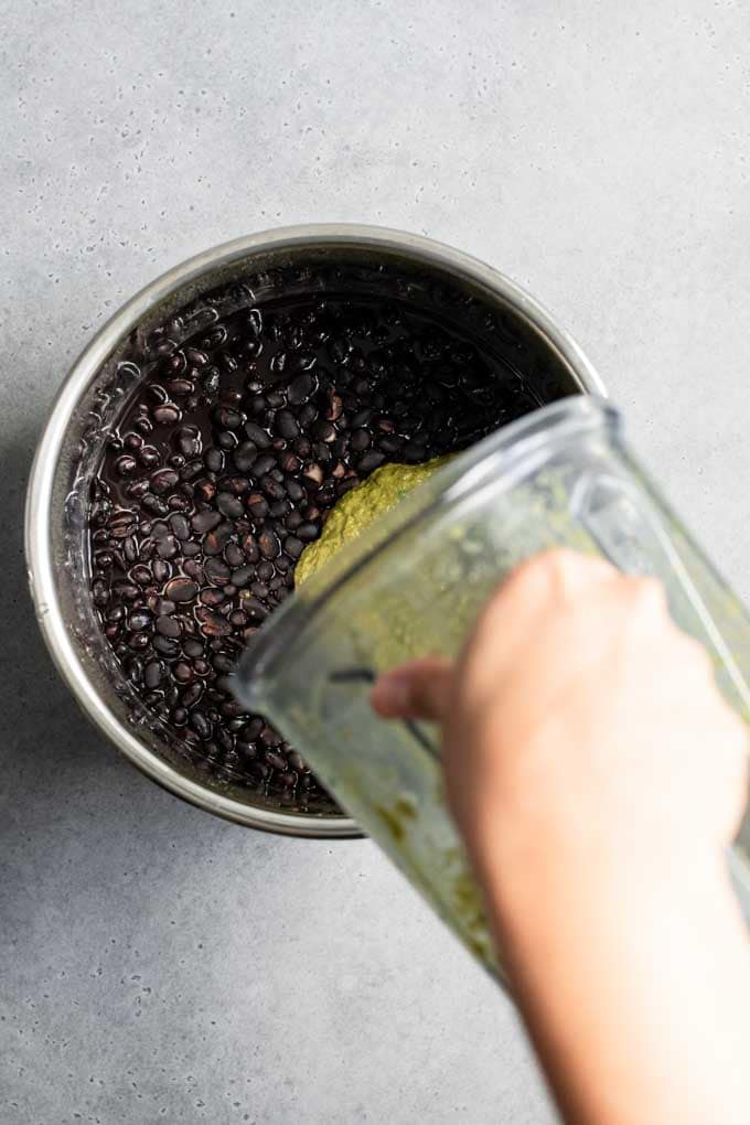 pouring seasoning into black beans
