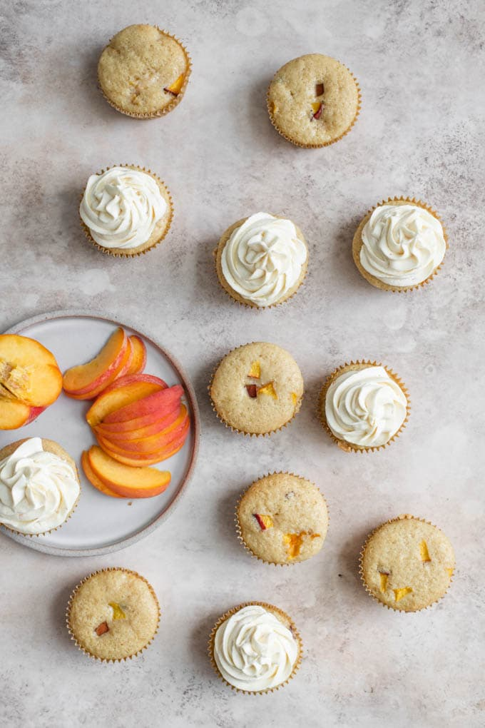 overhead photo of peach cupcakes, half of them frosted, with a plate of sliced peaches