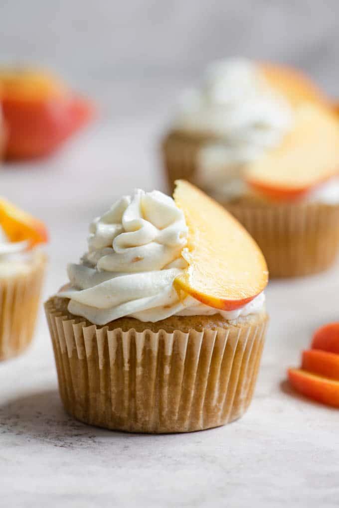 close up of a single peach cupcake