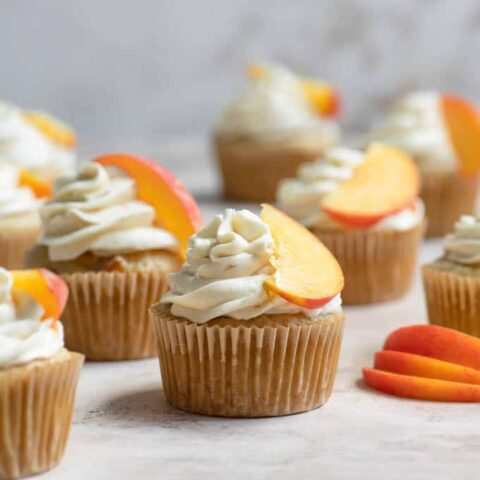 peach cupcakes frosted with a peach slice resting on frosting