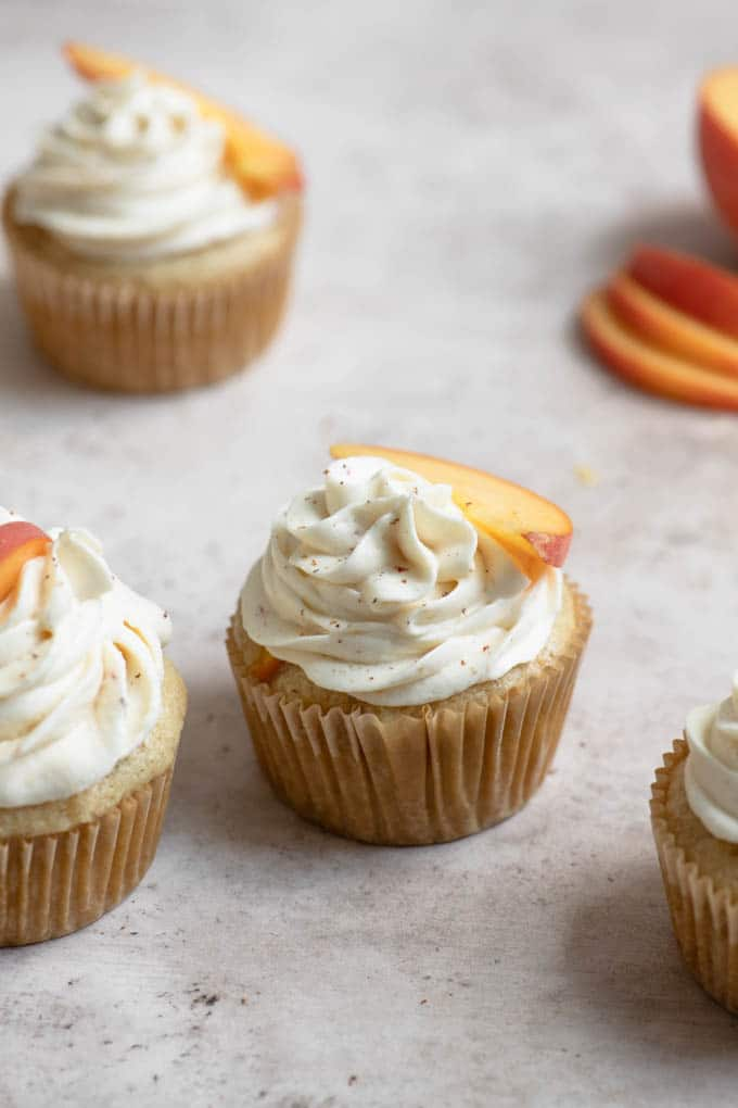 3 peach cupcakes and some sliced peaches