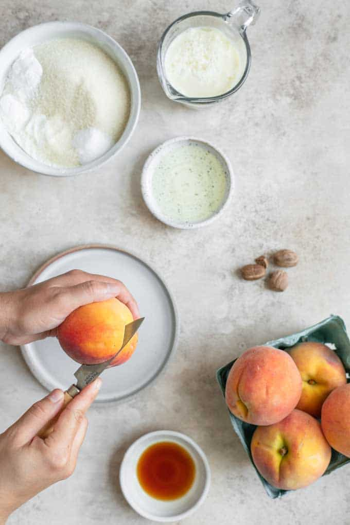 cutting a peach over a plate with the cake ingredients in photo
