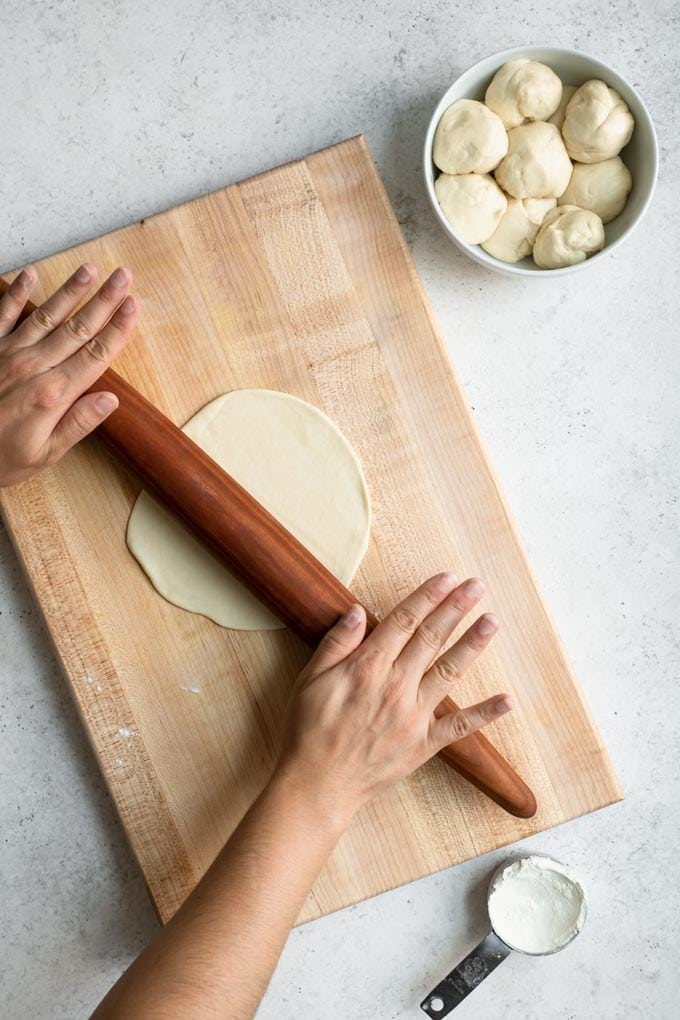 rolling out a flatbread on a wood cutting board with a rolling pin