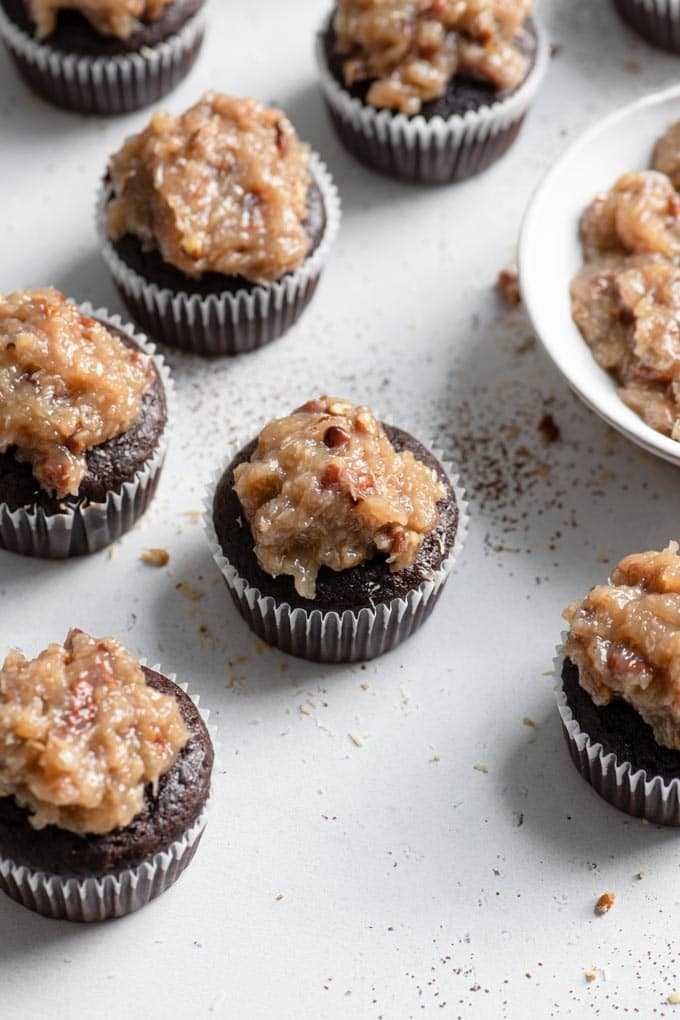 vegan german chocolate cupcakes with small bowl of frosting