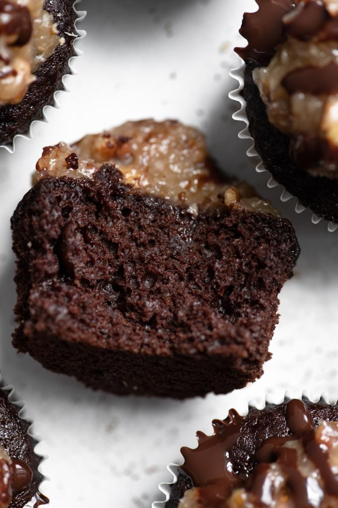 close up of german chocolate cupcake on its side with a bite taken out of it showing the crumb
