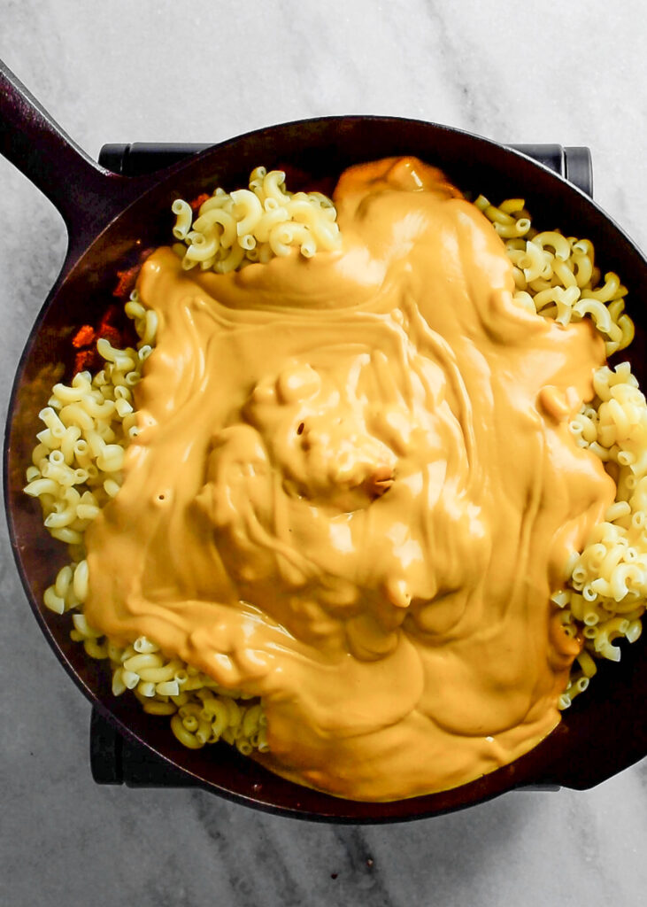 cheese sauce poured on macaroni in skillet