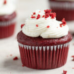 vegan red velvet cupcake sprinkled with red cake crumbs on top of the frosting