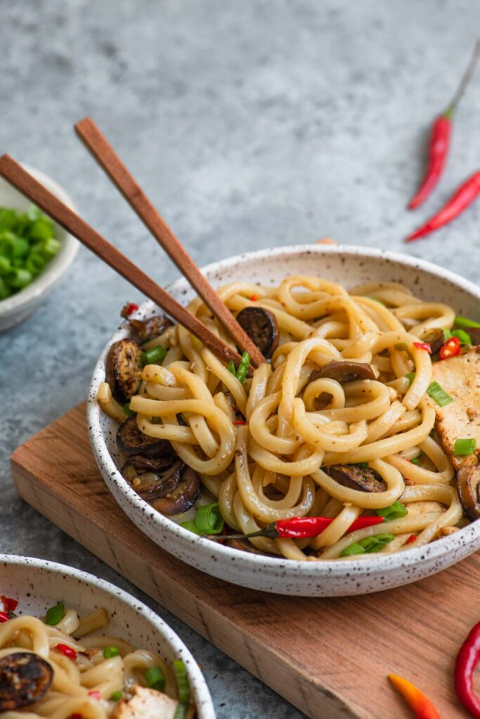 spicy sichuan noodles with eggplant in a bowl with wooden chopsticks