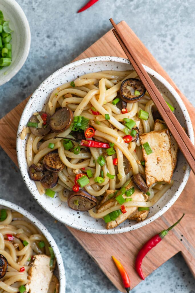 overhead shot of sichuan noodles with eggplant garnished with Thai chilies and green onions