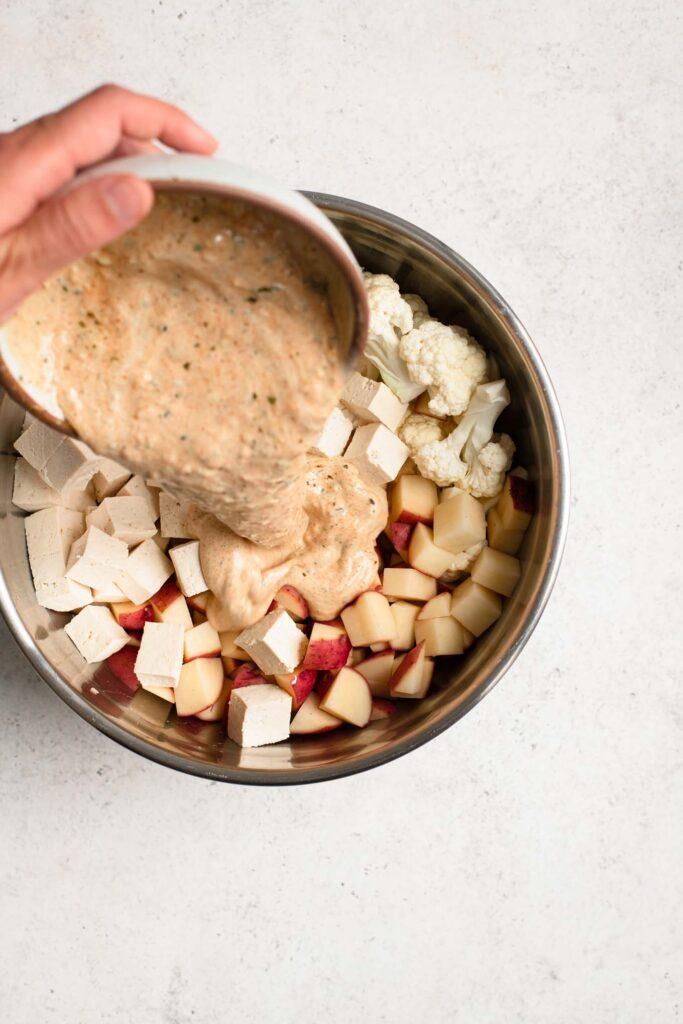 pouring tandoori yogurt sauce over cut tofu, potato, and cauliflower