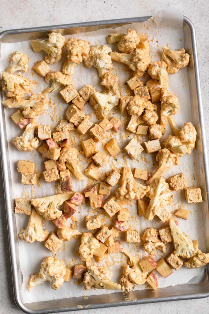 tofu, cauliflower, and potato spread over baking sheet before baking