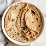 cooked roti with three folded partway over, stacked in tortilla warmer